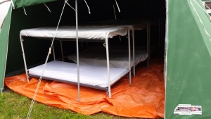 8 personen slapen op stapel bedden in onze tent.